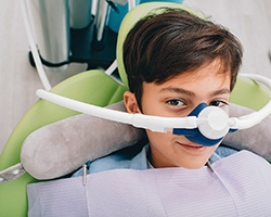 A young boy seated in the dentist's chair wearing a nasal mask in preparation to receive nitrous oxide