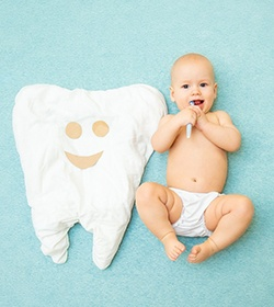 A baby with a toothbrush in its mouth and lying next to a pillow that looks like a tooth