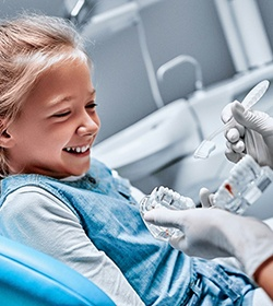 A young girl watching a dentist properly brush a mouth mold to show her the proper technique