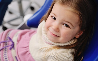 A little girl wearing a sweater dress and smiling after seeing a dentist for kids in Birmingham