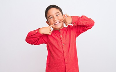 A young boy wearing a red button-down shirt and pointing to his healthy smile