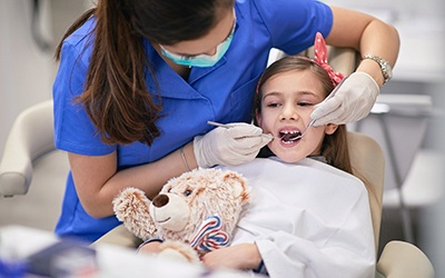 A young girl holding a teddy bear while allowing a dentist to check her smile