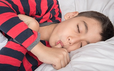 A young boy wearing a black and red striped shirt asleep in bed and sucking his thumb