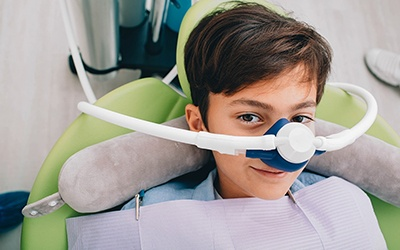 A young boy sitting in the dentist's chair preparing to receive nitrous oxide