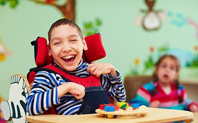 A young boy wearing a striped shirt and seated in a wheelchair playing with toys