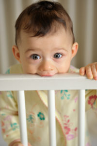baby with developing teeth teething on crib rail