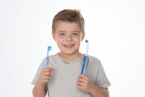 A child holding a manual and electric toothbrush.
