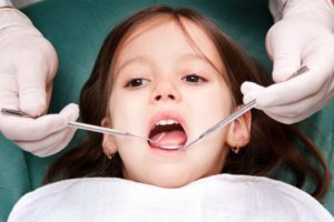 little girl mouth open dental checkup