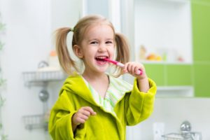 little girl smiling brushing teeth