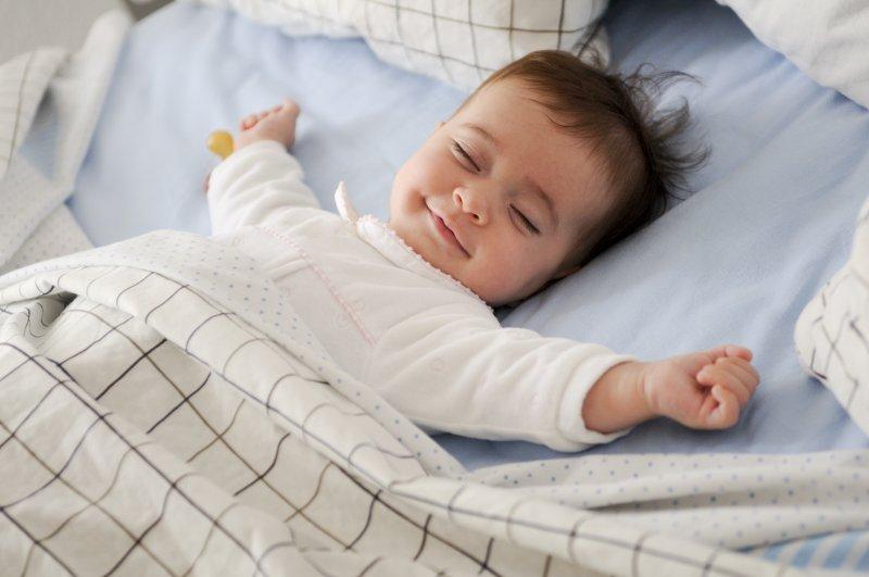 Sleepy baby smiling in bed
