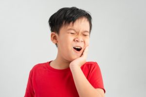 a child holding their mouth in pain because they have a tooth infection
