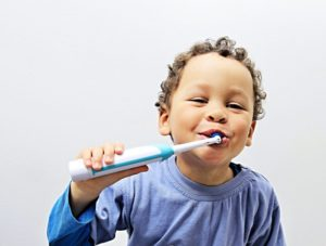 little boy brushing his teeth with an electric toothbrush
