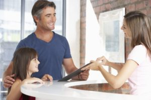 Father and daughter talking with receptionist about maximizing child's dental insurance coverage